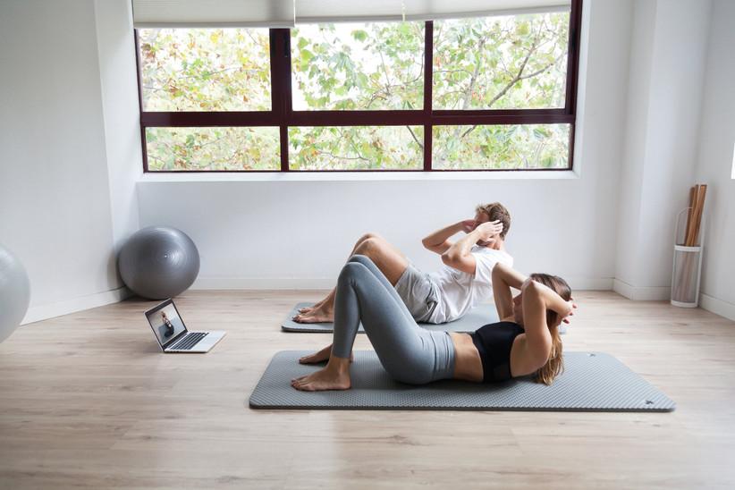 Pareja haciendo ejercicio en casa con clases a distancia antes de la boda