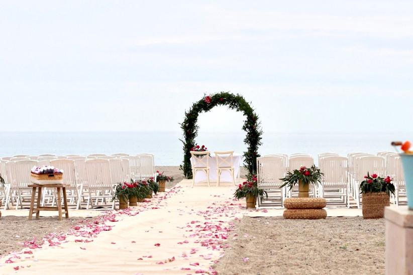 decoración para bodas en la playa con un bonito arco floral, un camino hasta el altar hecho de tela y pétalos y sillas blancas