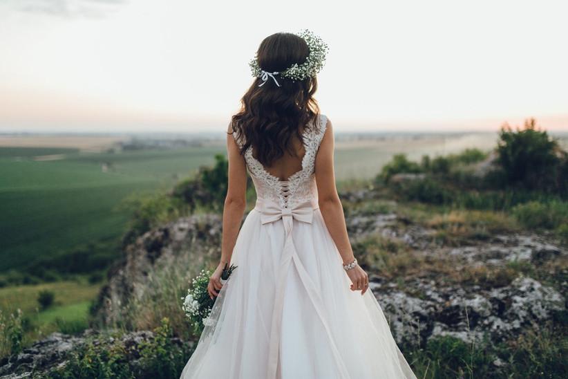 novia con el pelo suelto ondulado y corona de flores, en la sesión de fotos de la boda al aire libre