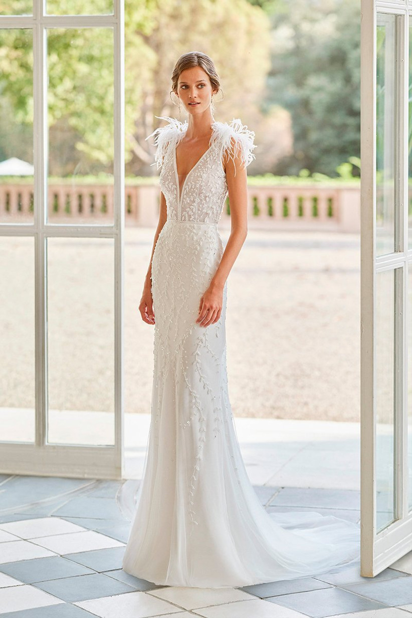Vestido de novia de corte sirena con escote en V y plumas en los hombros de la colección Gatsby de Rosa Clará 2022