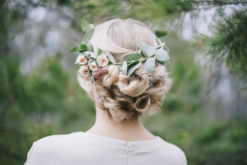 recogido de novia para pelo rizado con corona de flores, ideal para el look nupcial de una novia romántica el día de la boda