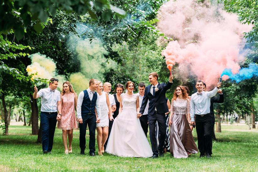 Pareja de recién casados con amigos y humo de colores el día de la boda