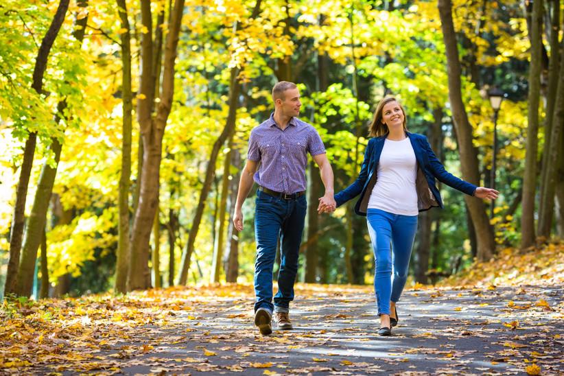 Pareja feliz paseando por un parque cogidos de la mano antes de la boda