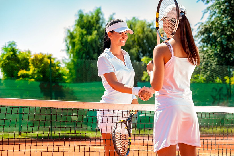Amigas se saludan antes de un partido de tenis después del día de la boda