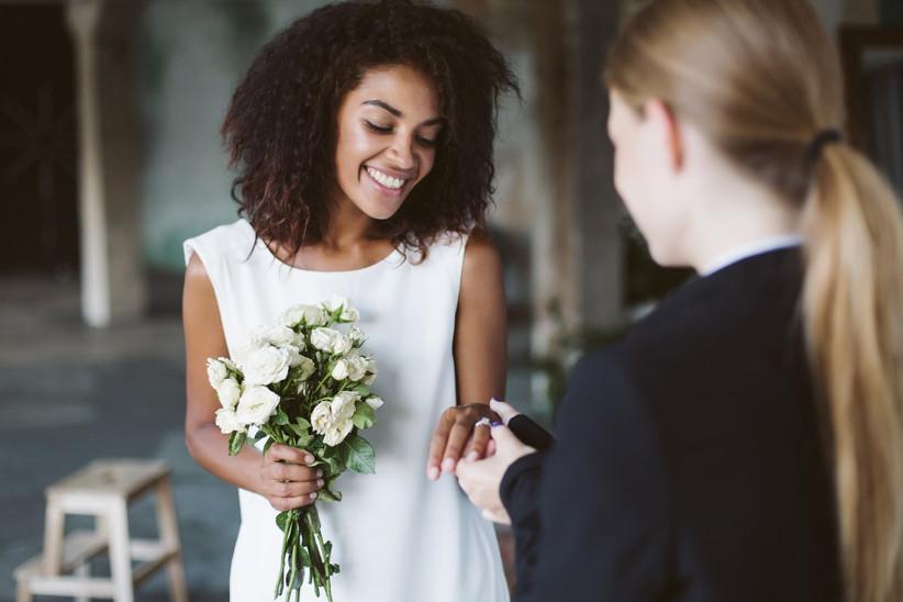 novia afro en la ceremonia de la boda recibiendo el anillo de casada por parte de su prometida