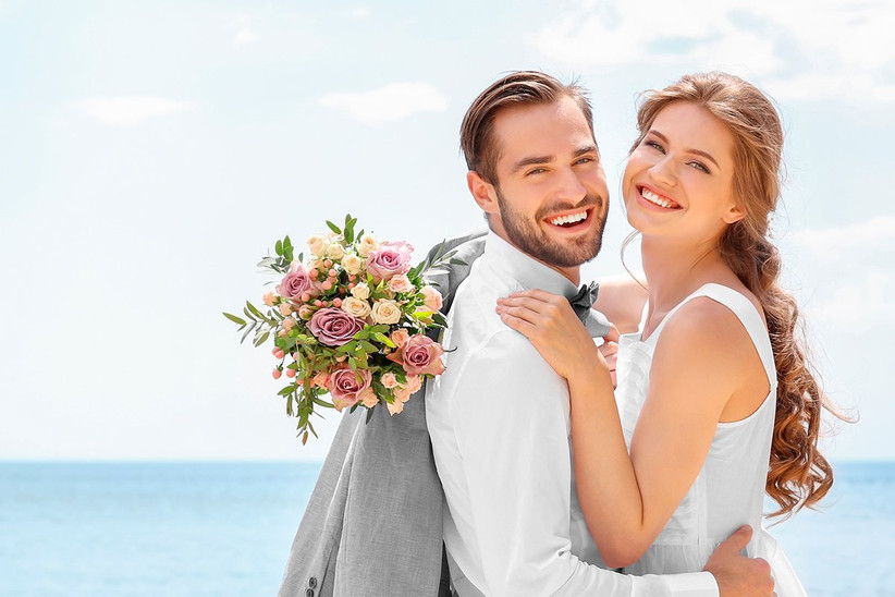 Pareja feliz y abrazada, el día de su boda, después de haber hecho un blanqueamiento dental