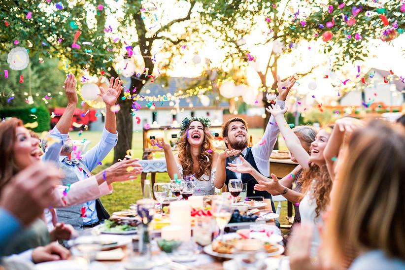 Pareja feliz rodeada de amigos durante el banquete nupcial el día de la boda