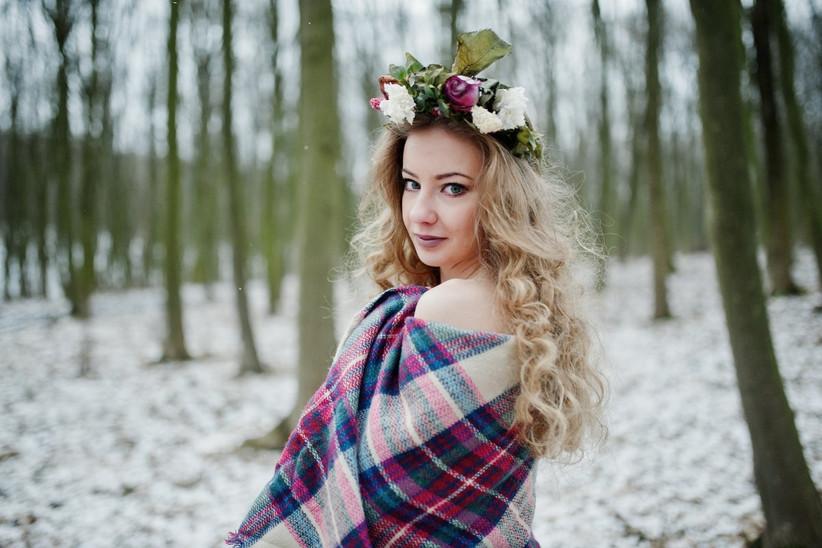 novia de pelo rizado con corona de flores en mitad del bosque nevado el día de su boda de invierno