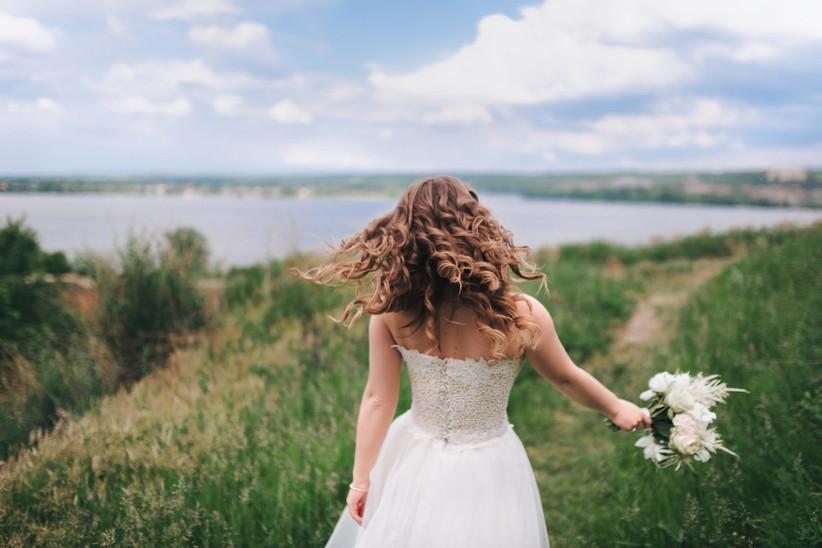 Novia con el pelo rizado el día de su boda en el campo