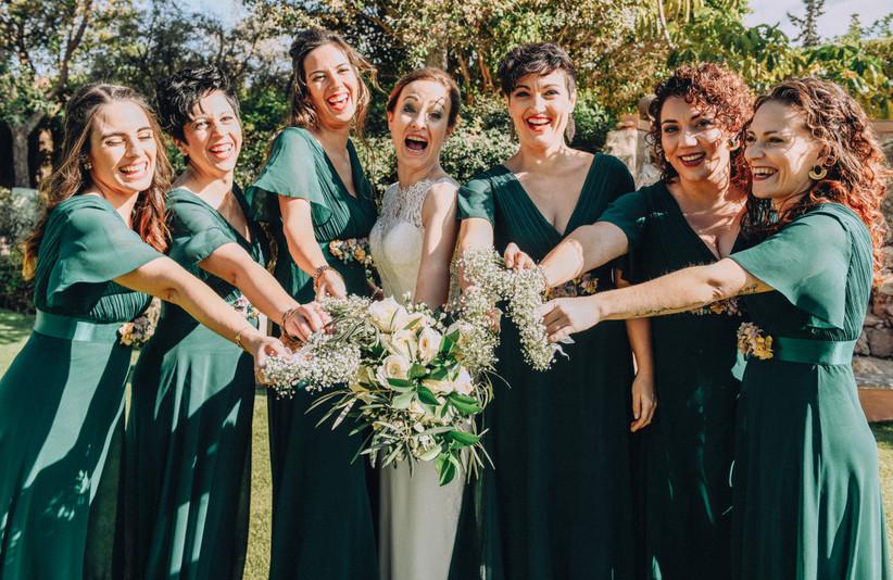 Damas de honor muy sonrientes el día de la boda, enseñando el ramo de novia y las pulseras o corsages de damas de honor