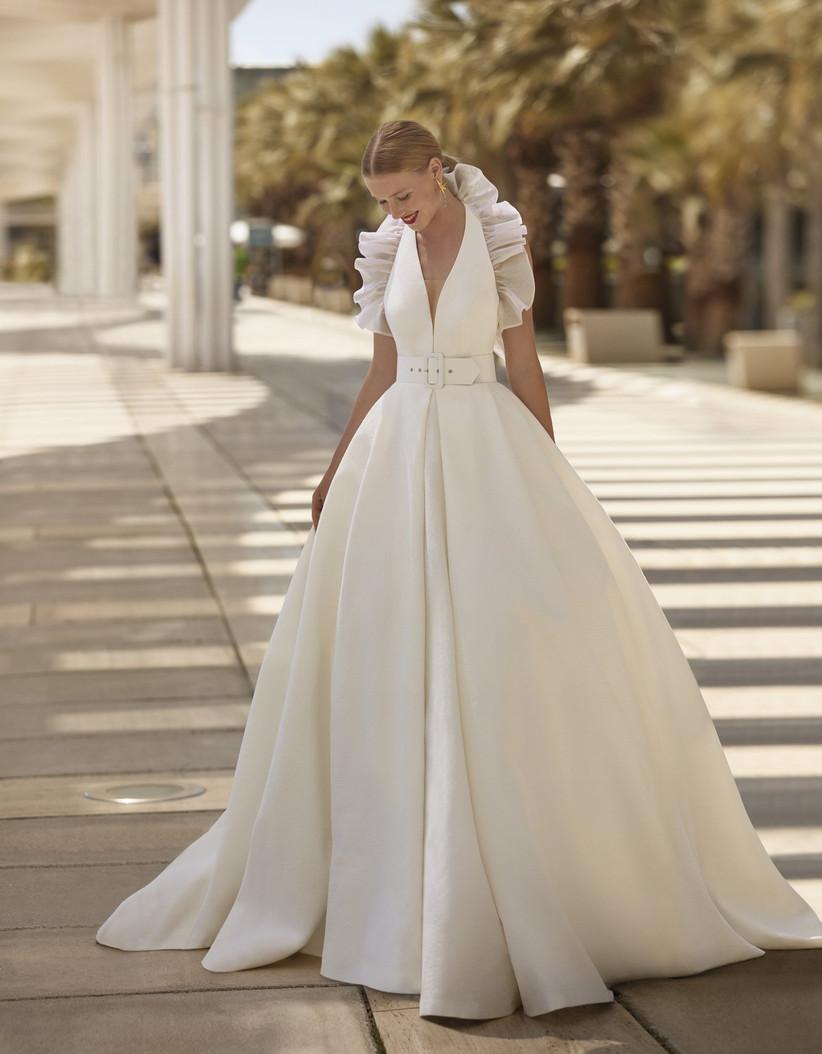 vestido de novia princesa de la colección Brisa de Manu García 2022 con escote en V y volantes y cintura entallada con cinturón