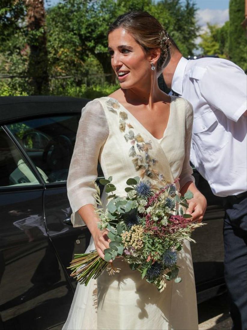 Detalle de las flores en tonos pastel del vestido de novia de María Corsini y su ramo de novia silvestre