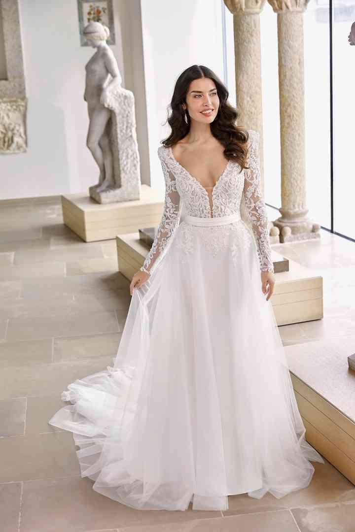vestido de novia con sensual escote, mangas largas y falda al vuelo de la colección 2022 de Ronald Joyce, ideal para la boda