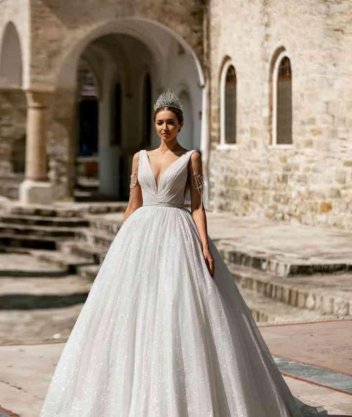 vestido de novia con falda princesa y escote pronunciado en V con toques glam de la colección 2022 de Monica Loretti, ideal para la boda