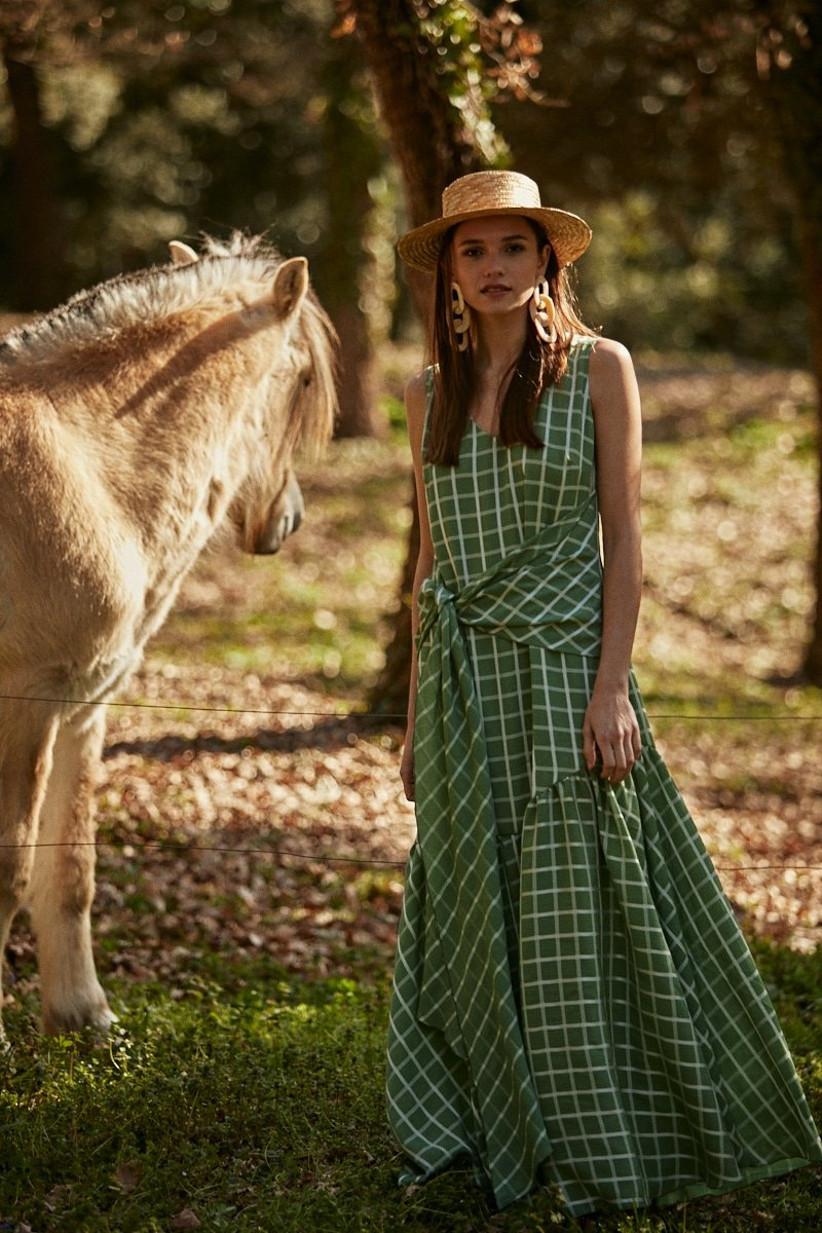 vestido de invitada en color teja de Clotilde 2021 con mucha caída y movimiento adornado con un espectacular sombrero