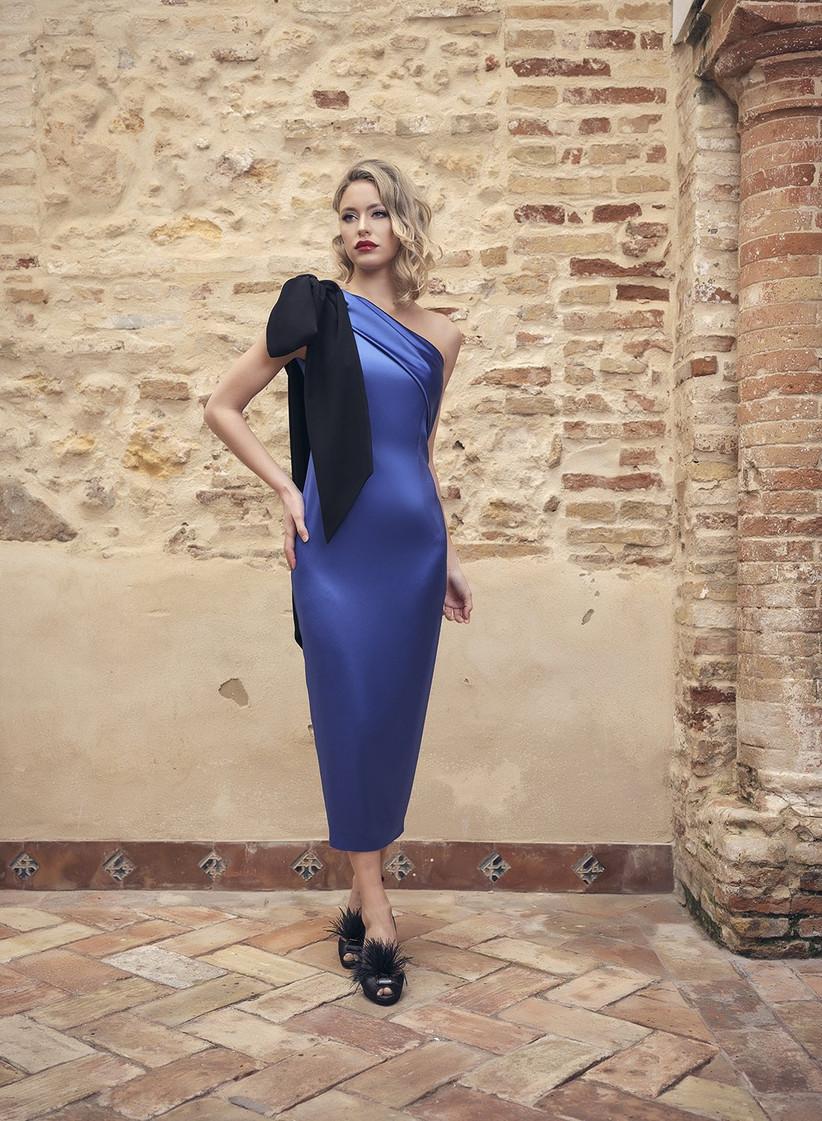 vestido de fiesta Nuribel 2021 en azul cobalto que lleva un lazo negro en el escote para ir a la última moda