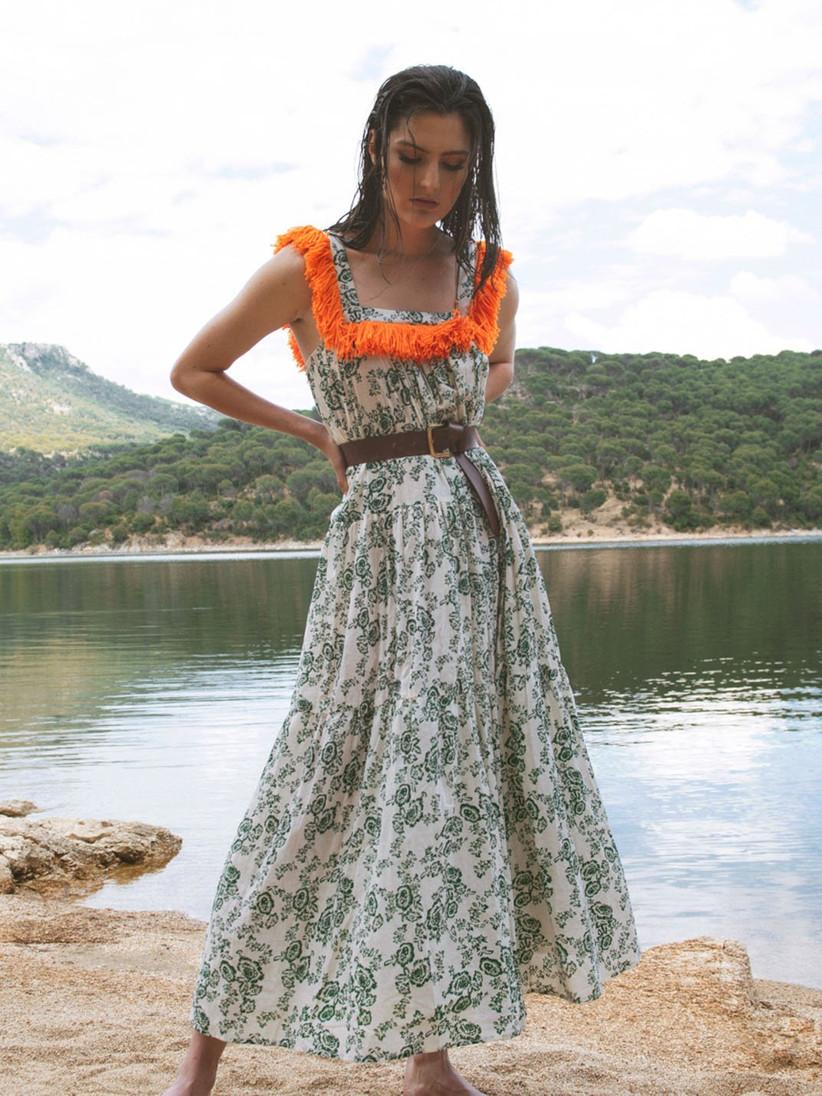 vestido de fiesta de The IQ Collection 2021 de estilo boho chic con estampado floral verde y flecos naranjas en la zona del escote y de la espalda