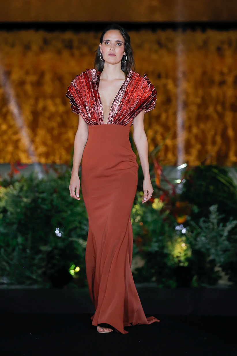 Vestido de fiesta en color naranja con juego de tejidos entre el escote moderno y la falda lisa, de Carla Ruiz 2022, ideal para una boda