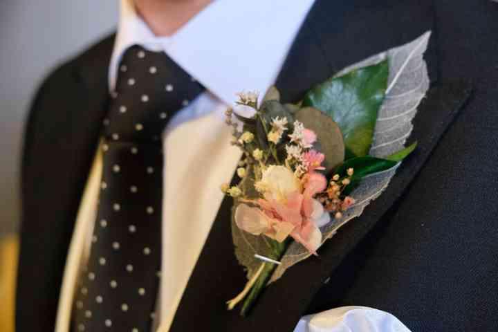 Prendido o boutonnière en el ojal del traje de novio el día de la boda