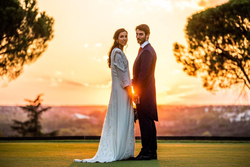 Pareja durante el reportaje fotográfico, durante la puesta de sol, el día de la boda