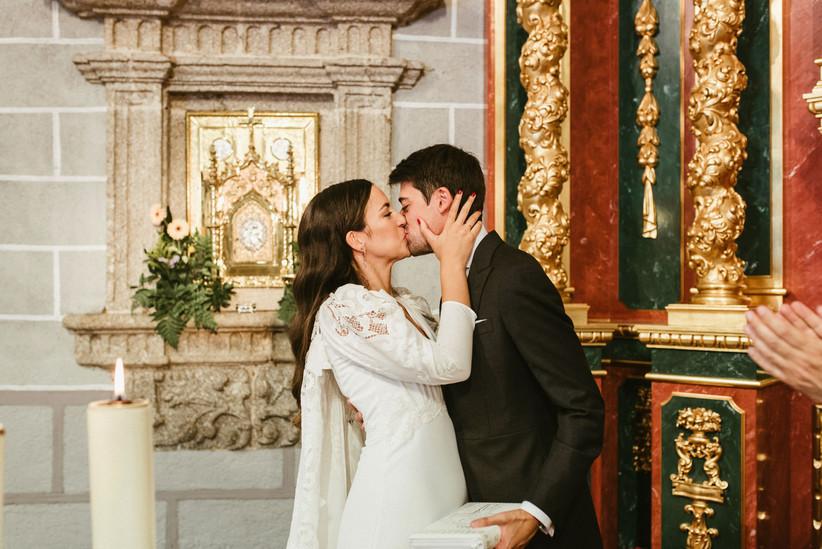 Pareja besándose en el altar de la iglesia después de la ceremonia religiosa el día de la boda