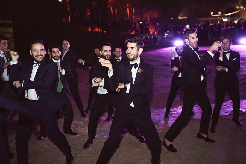 el novio y sus amigos vestidos de gala bailando durante la fiesta de la boda