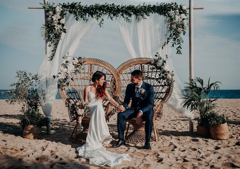 Paraeja en el altar de su ceremonia civil en la playa con flores y telas blancas el día de la boda