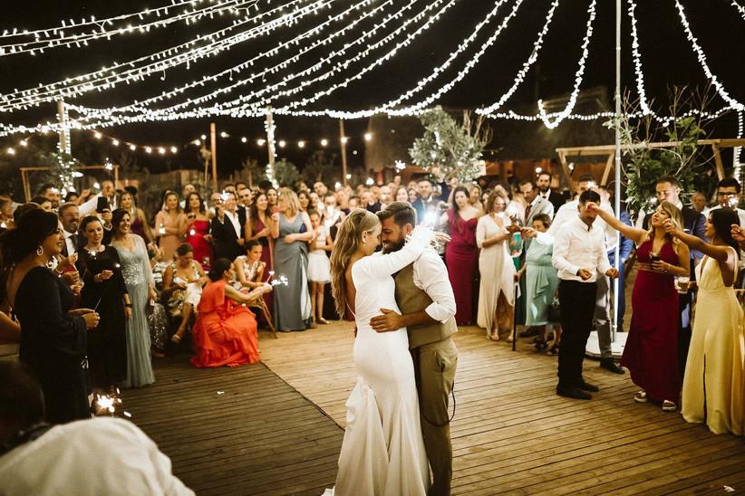Baile de recién casados en la playa el día de la boda bajo un cielo estrellado de luces y bengalas sujetadas por los invitados