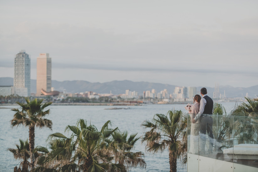 Pareja el día de su boda contemplando la ciudad de Barcelona desde la terraza de un hotel urbano en Barcelona