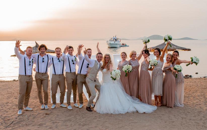 Pareja de recién casados junto a sus best man y damas de honor en playa el día de su boda