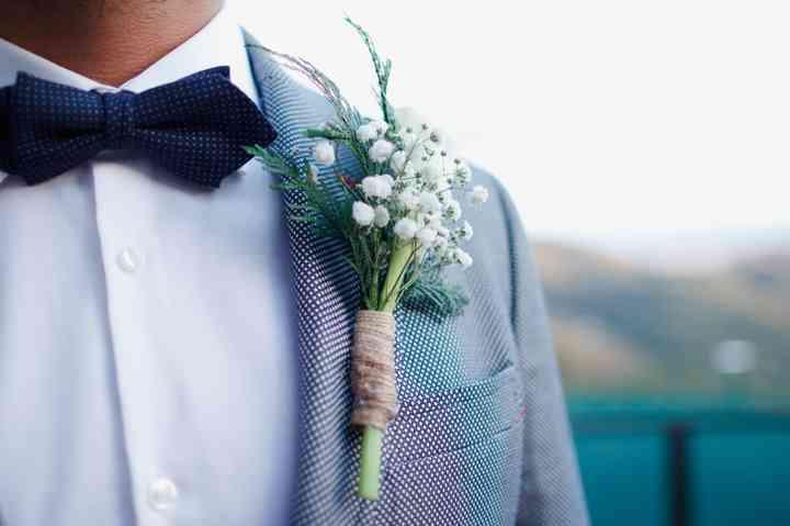 Prendido o boutonnière de aire silvestre en el traje de novio el día de la boda