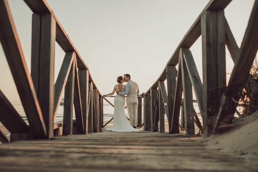 Pareja bersándose y llevando sendos outfits nupciales frescos y ligeros para su boda en verano