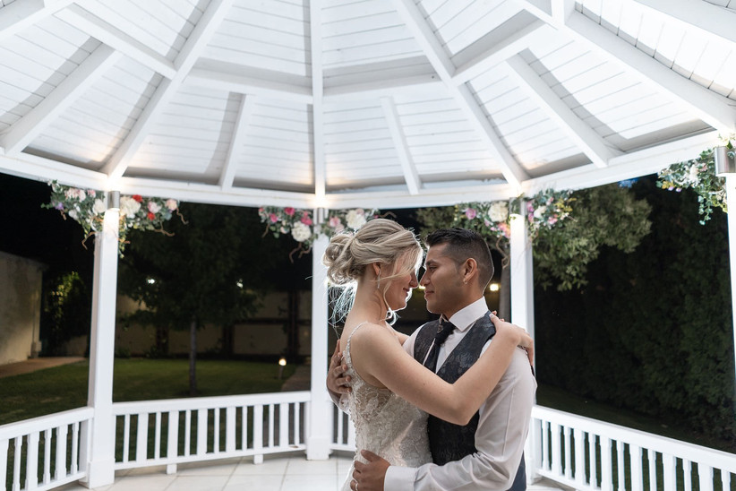 Pareja bailando el día de la boda mientras se mira fijamente a los ojos
