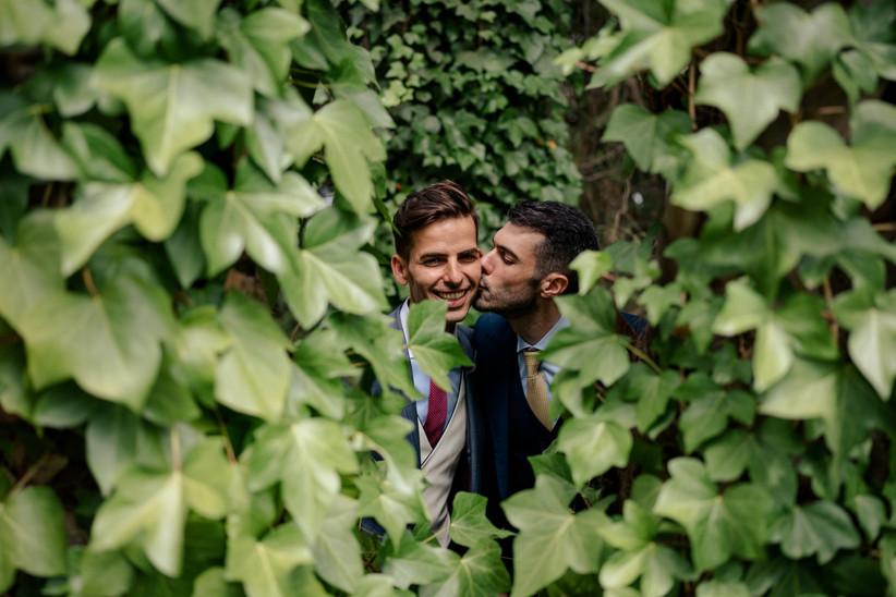 Pareja LGTBI+ dándose un beso durante la sesión fotográfica el día de la boda
