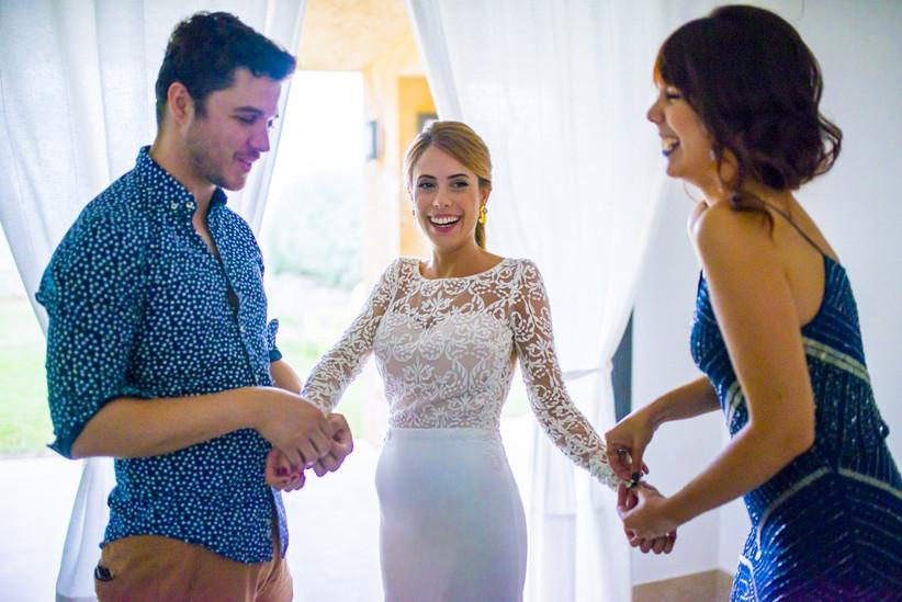 Novia arreglándose con la ayuda de sus hermanos el día de la boda