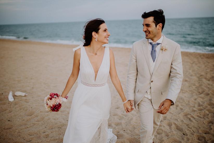 Pareja feliz paseando por la playa durante la sesión fotográfica el día de su boda en verano