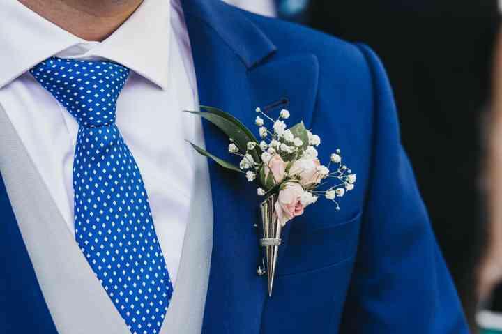 Prendido o boutonnière en rosa, blanco y verde en el traje de novio el día de la boda