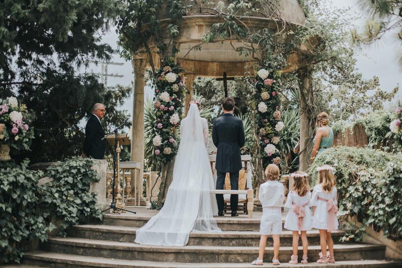 Un momento de la ceremonia civil al aire libre el día de la boda con la pareja de espaldas