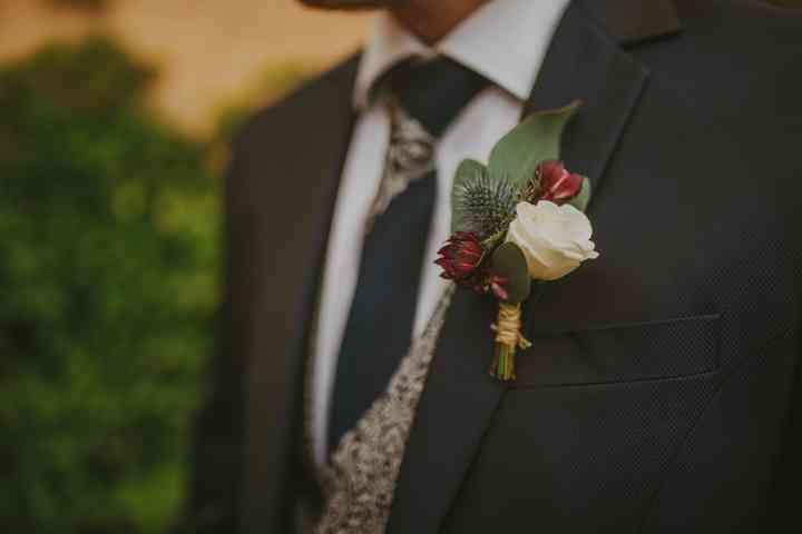 Prendido o boutonnière ya puesto en el ojal de la americana del traje de novio el día de la boda