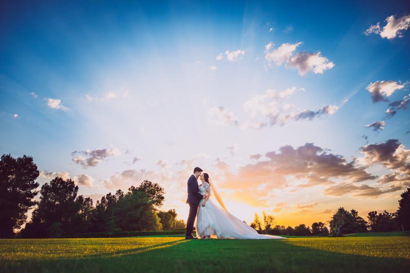 Pareja abrazada el día de la boda con la puesta de sol de fondo