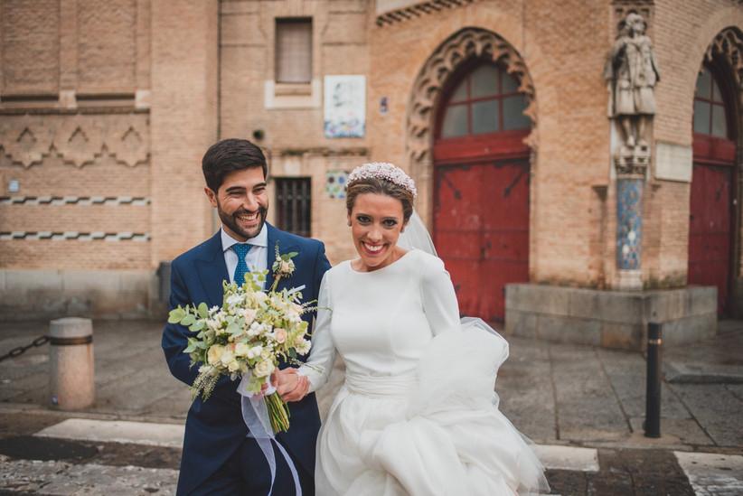Pareja mira sonriente a la cámara fotográfica del fotógrafo de bodas el día de la boda