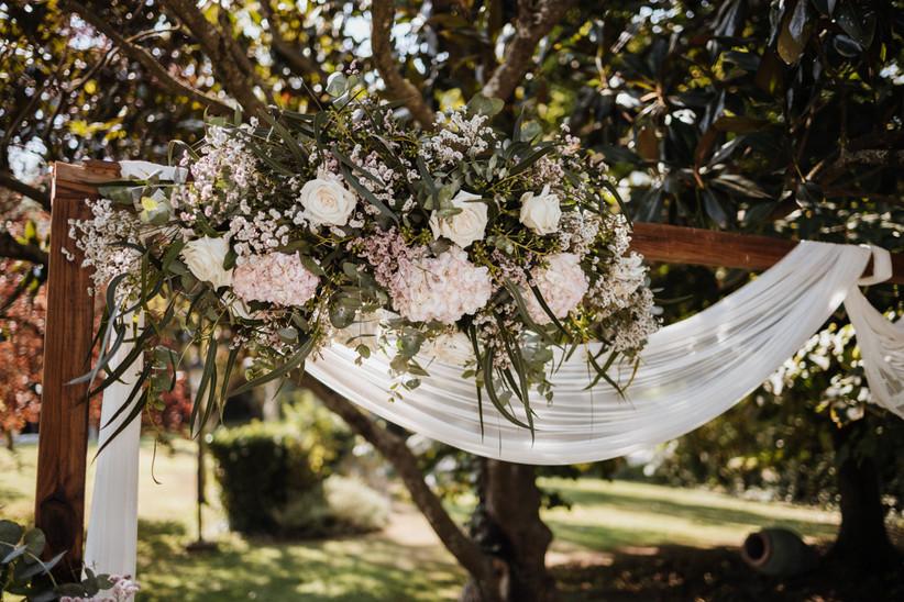 Arco de flores blancas y rosas con telas livianas blancas