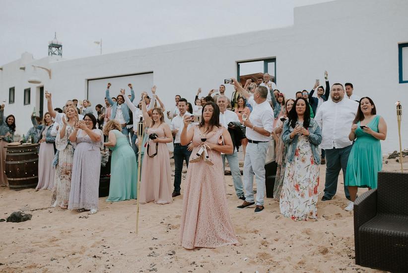 Invitados vestidos de fiesta durante el aperitivo de una boda en la playa