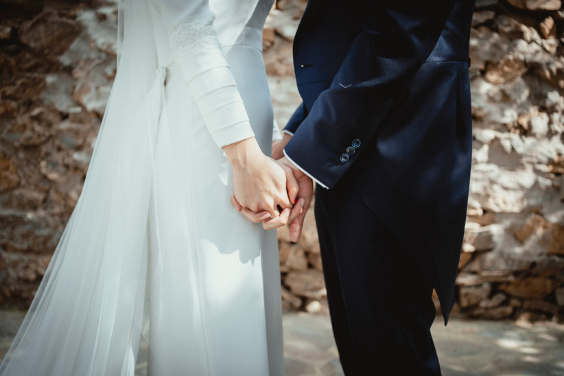 Pareja enamorada el día de su boda con las manos entrelazadas