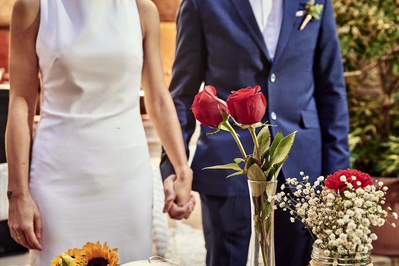 Pareja cogida de la mano en el altar después de haber intercambiado las rosas durante la ceremonia de la rosa el día de la boda