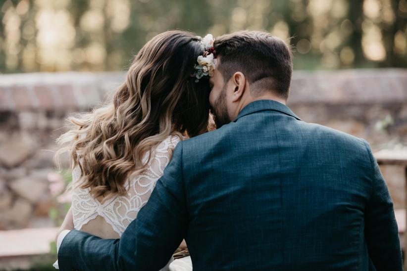 muestras de complicidad y afecto de una pareja de espaldas el día de su boda