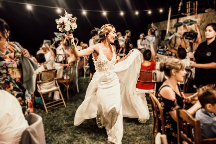 novia divertida con el ramo en la mano durante el banquete de su boda