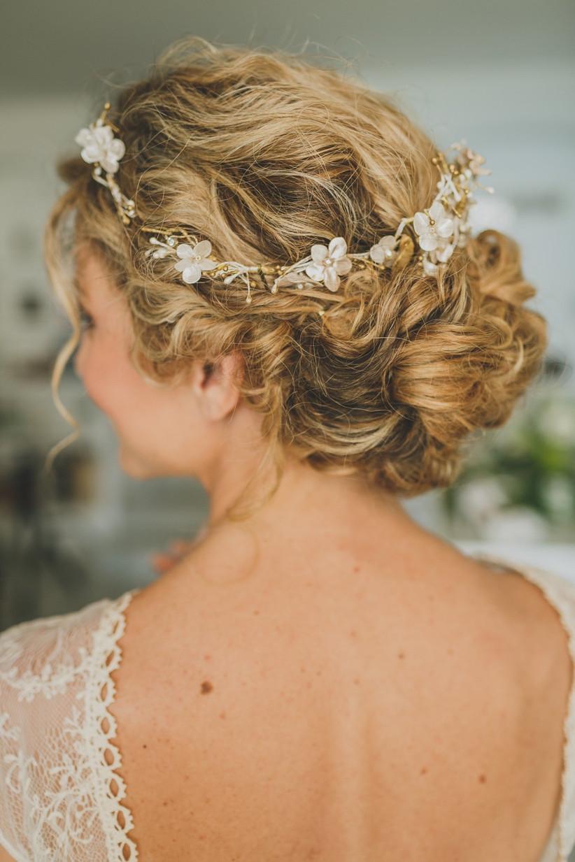 moño de novia con pelo rizado y corona de flores romántica, ideales para el día de la boda
