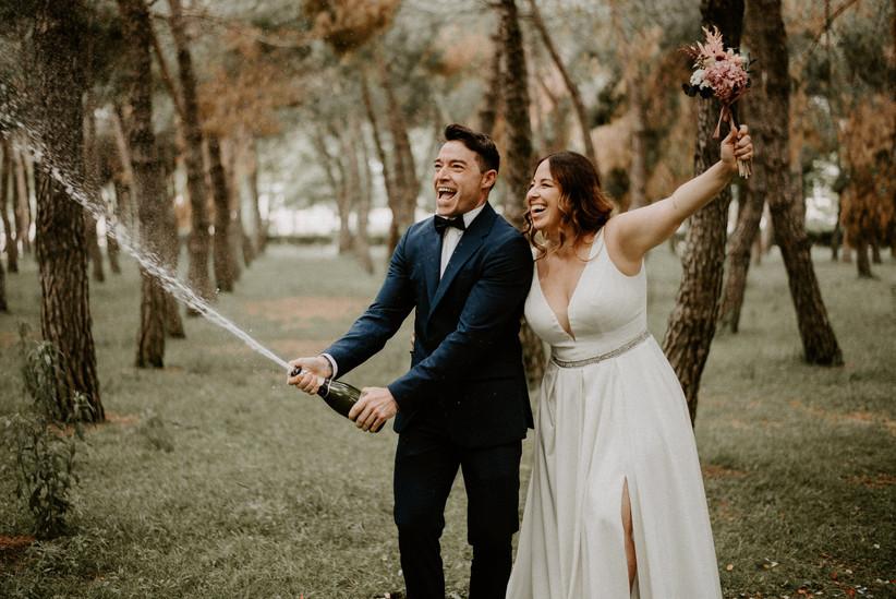 pareja de novios celebrando con cava la felicidad por haberse casado