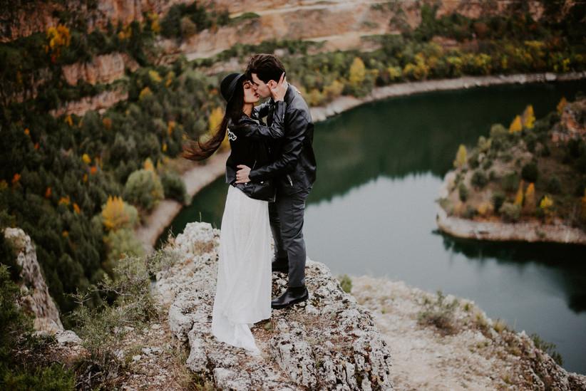 Pareja con cazadoras de cuero se besa durante la sesión de fotos en pareja el día de la boda